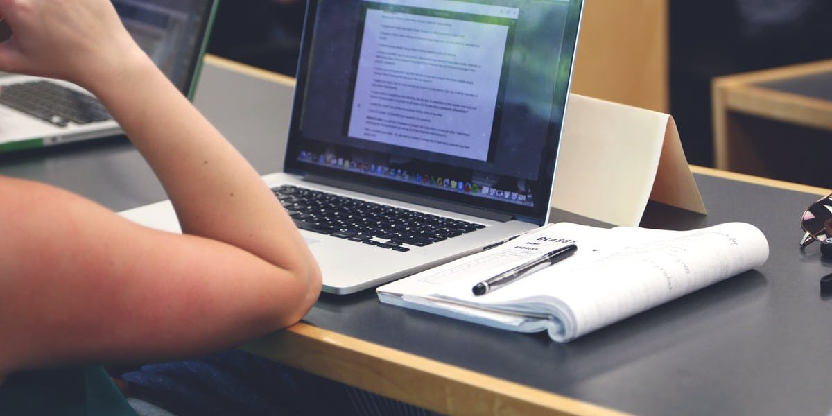 A person at a computer taking notes.
