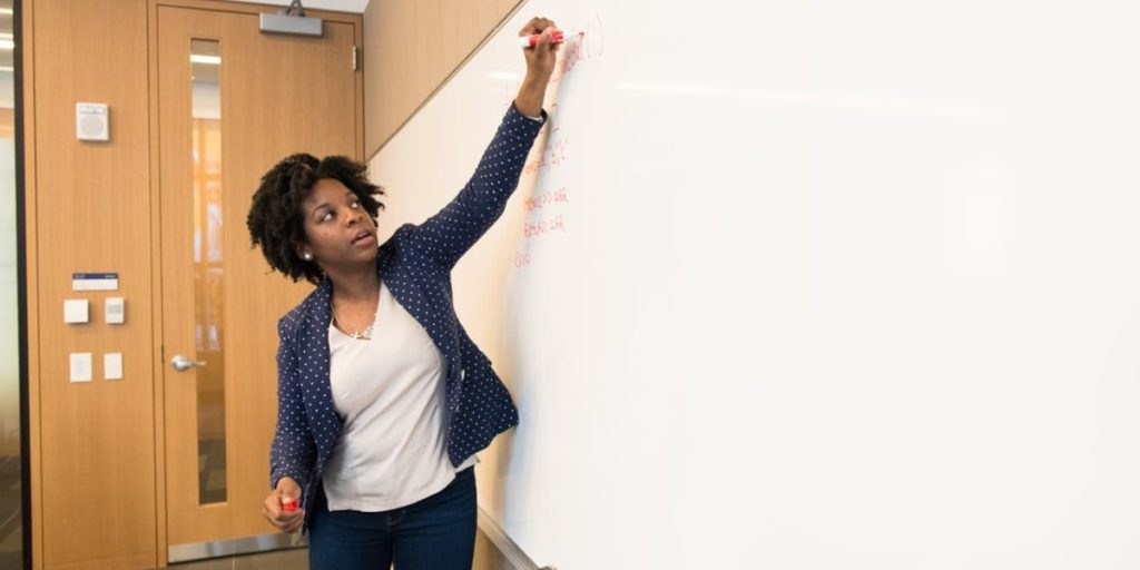 A teacher at a dry erase board leading a class.