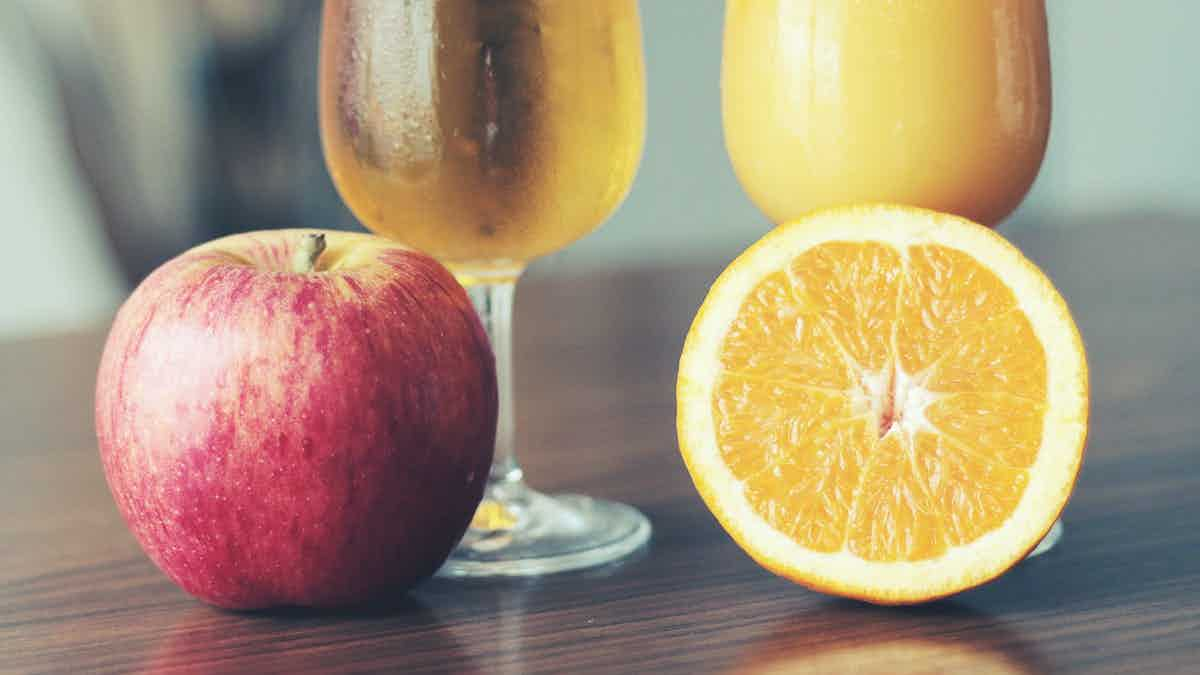 An image of an apple and an orange next to each other.