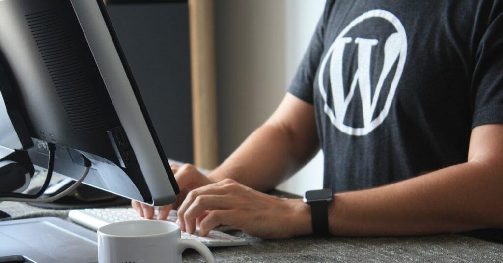 Developer at a computer wearing a WordPress t-shirt