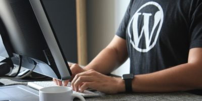 Developer at a computer wearing a WordPress t-shirt