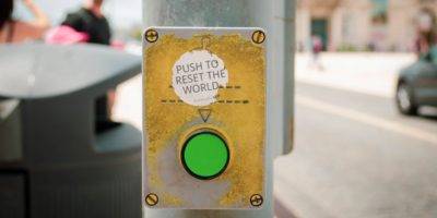 "green button on street crossing post with a sticker that says ""push to reset the world"""