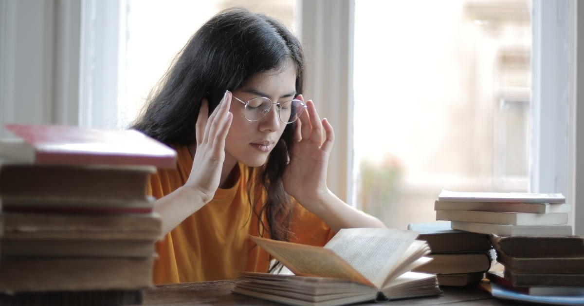 Students sitting in front of a book concentrating on her studies.