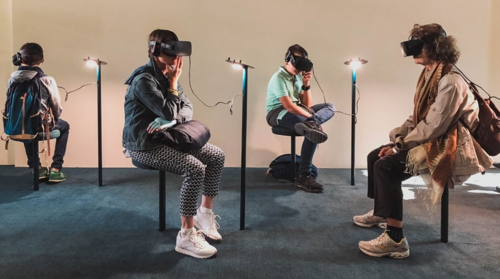 People sitting in a room wearing AR glasses.