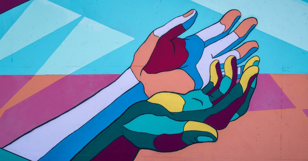 multi colored hands reaching up