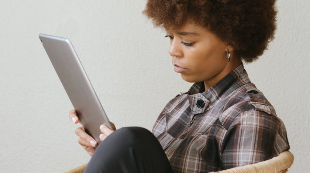 black woman reviewing a tablet while she conducts remote training