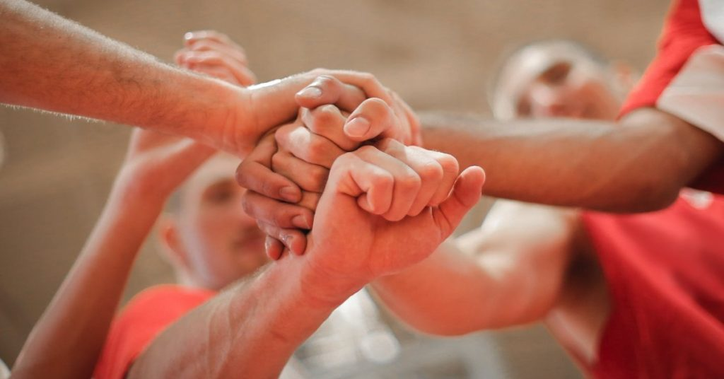 A group of teammates with fists together in solidarity