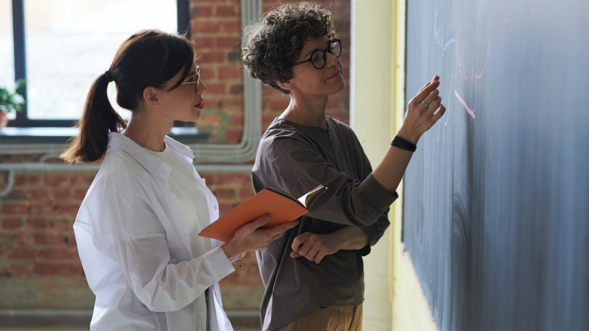 Two women examining a chalk board together.