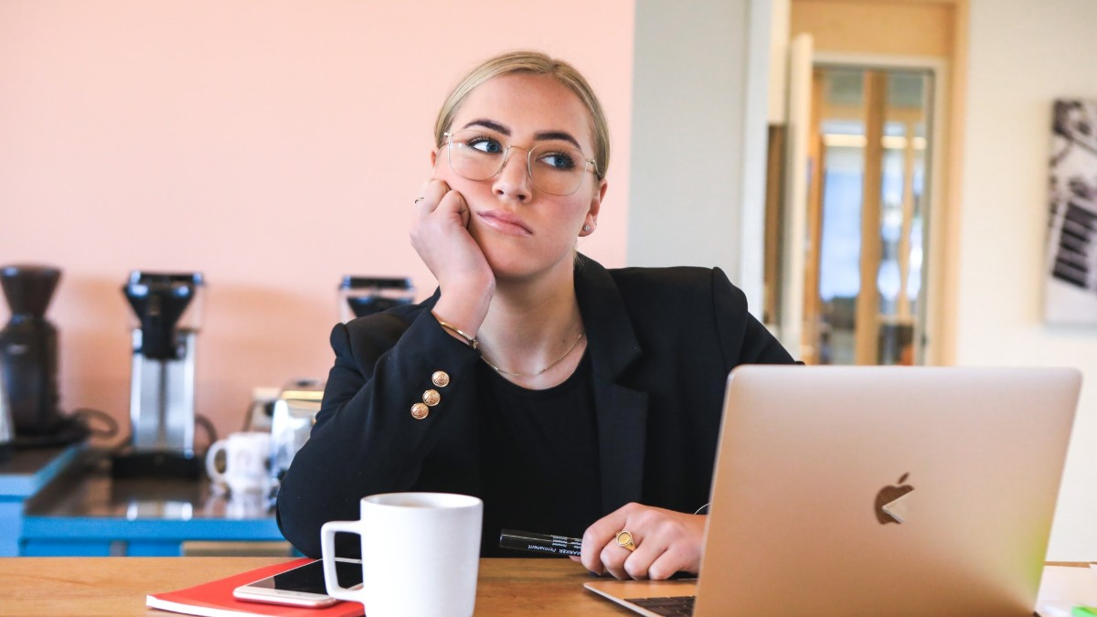 Woman procrastinating as she sits in front of a computer.