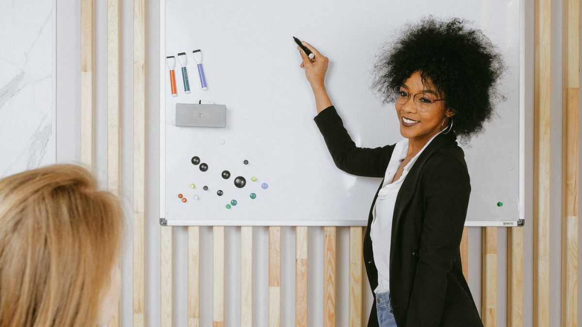 Woman in a meeting room in front of a whiteboard.