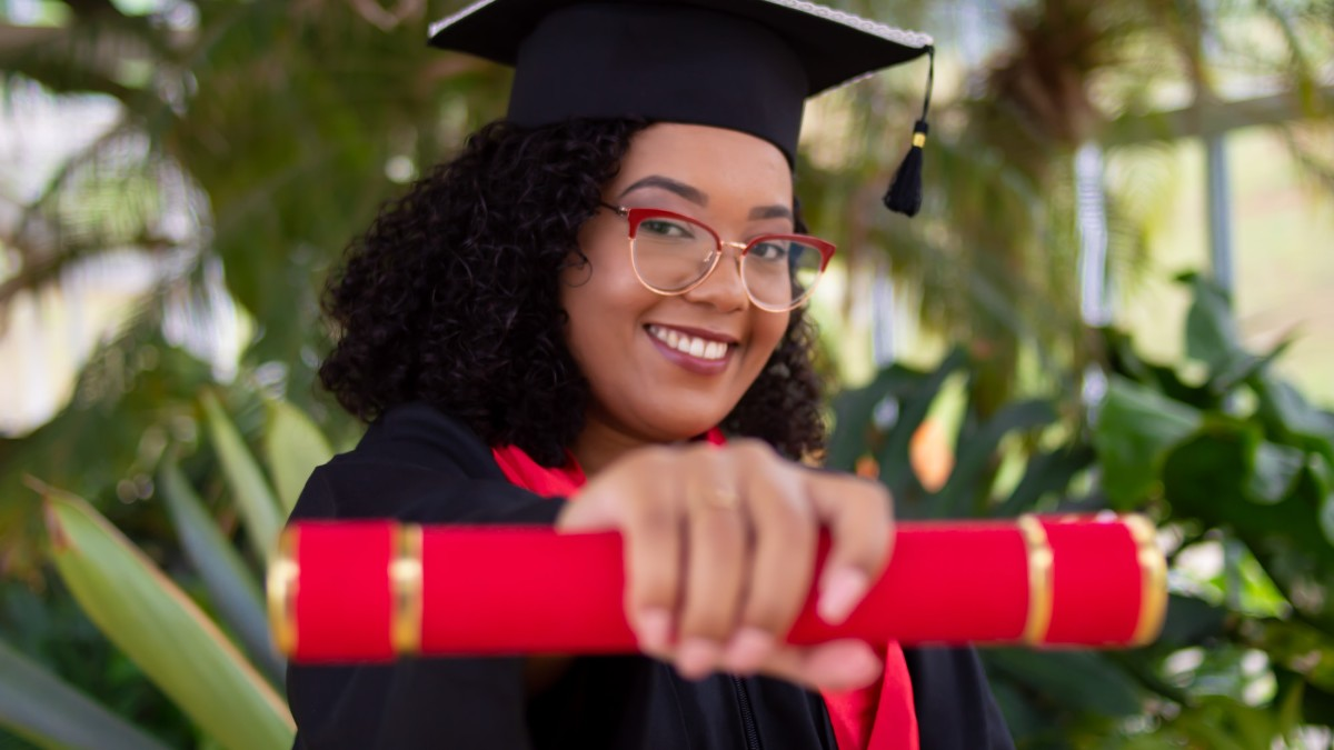 A woman holding out a diploma upon graduation.