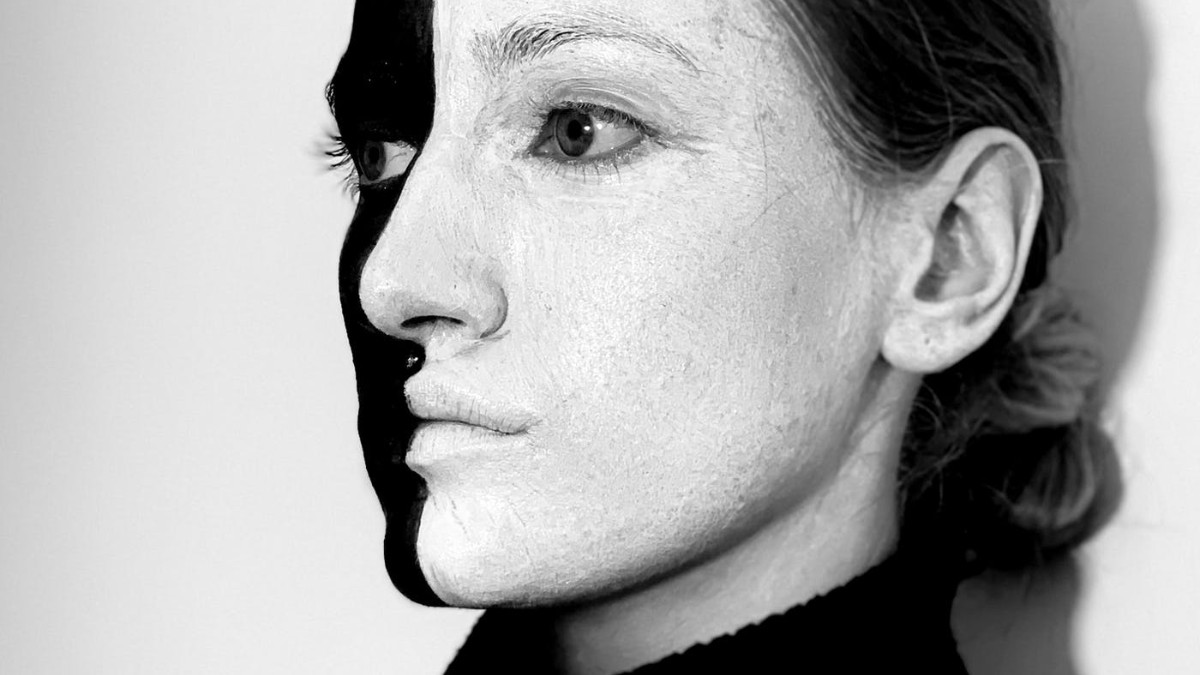 A woman in three quarters profile wearing a black turtleneck and face paint that covers her face in half white and half black paint.
