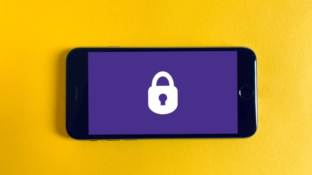 A smart phone with a purple screen showing a white lock on a yellow background.