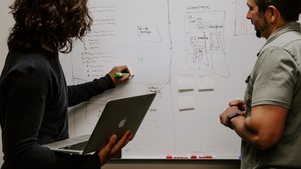 Two people standing in front of a blackboard, sketching out designs for webpage layout and site content.
