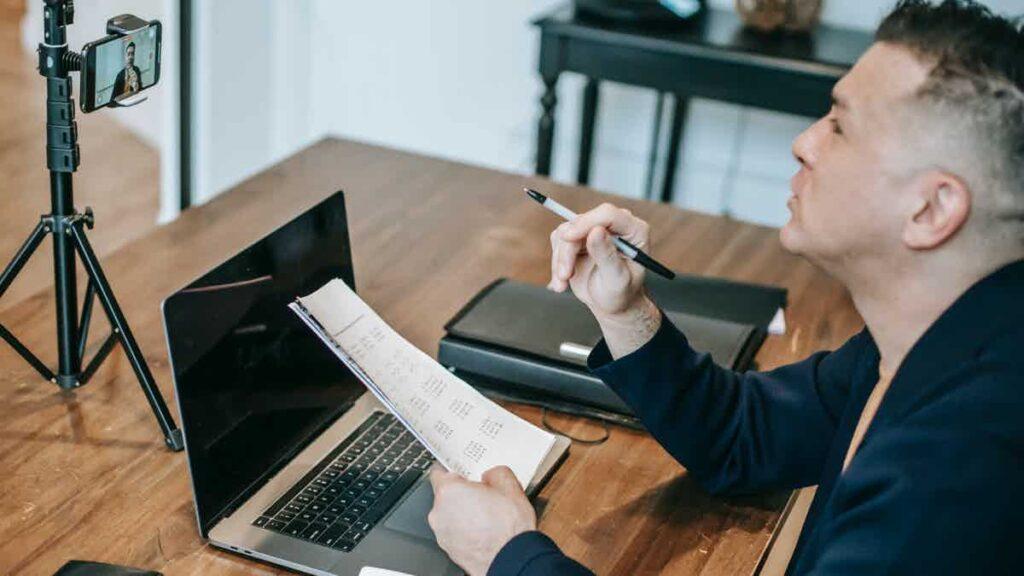 A teacher at a desk filming a course.