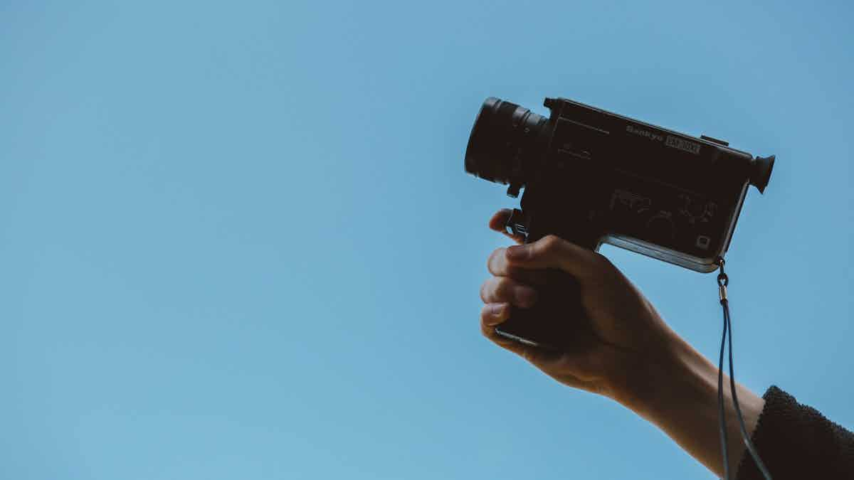 Hand holding a camera indicating online video shoot.