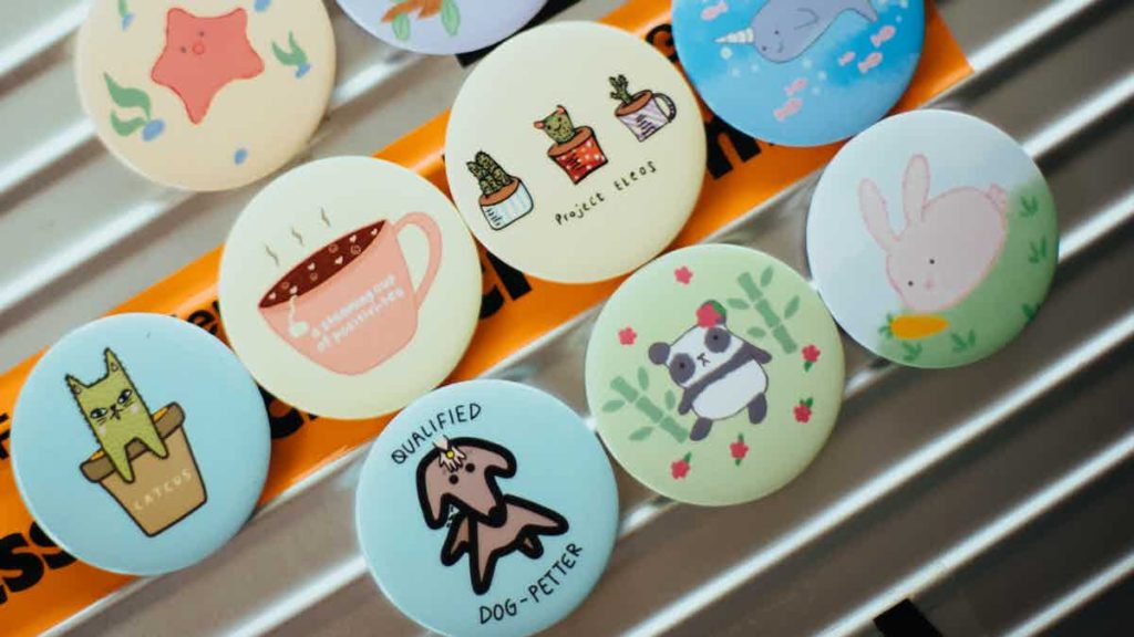 """A row of badges with cute images on them and titles such as """"qualified dog-petter"""""""