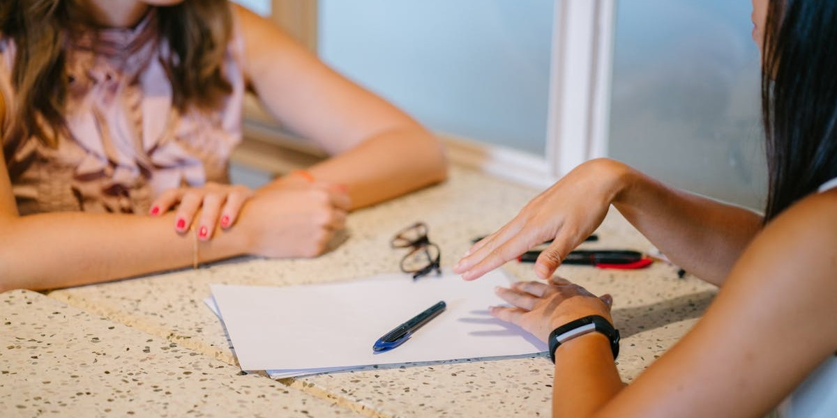 A student mentor at a desk discussing a paper with a learner.